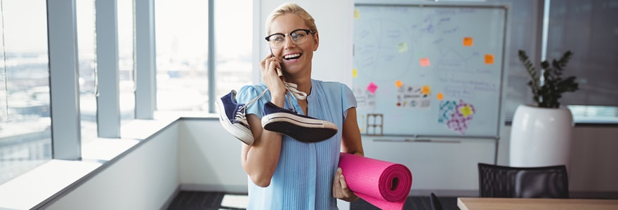 Smiling executive talking on mobile phone while holding exercise mat and shoes