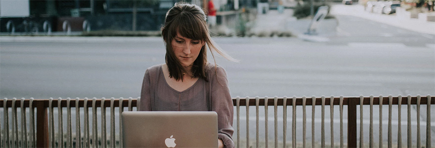 Woman working on MacBook outside cafe
