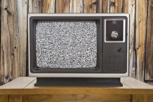 Old Television with Static Screen and Wood Wall