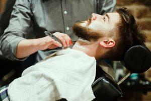 Barber shaving a bearded man