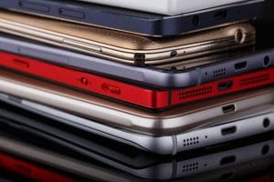Heap of electronical devices close up - smartphones on black background