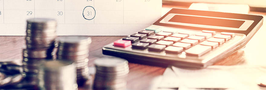Payroll picture featuring a calendar in the background, coins in the front and a calculator