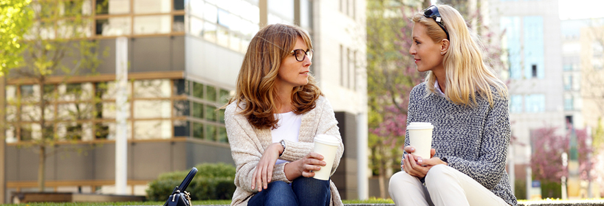 Portrait of two middle age women sitting at office park while on coffee break